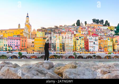 young woman enjoing Panoramic view of colorful houses in old town in Provence village Menton, France, French Riviera. Provence Alpes Cote de Azur. - Stock Photo