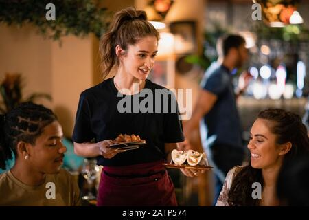 A waitress serving food to customers at a restaurant in Newcastle-Upon-Tyne. - Stock Photo