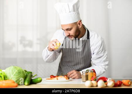 Chef Cooking Fish Squeezing Lemon On Salmon Steak In Kitchen - Stock Photo