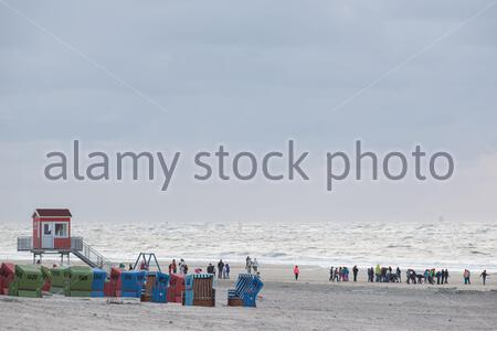 tourists on the beach of langeoog island with a lifeguard station and roofed wicker beach chairs - Stock Photo