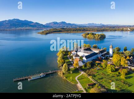 Steam jetty and Benedictine monastery Frauenwoerth on Fraueninsel, Frauenchiemsee, behind Krautinsel and Herreninsel, Chiemsee, Alps, Chiemgau - Stock Photo