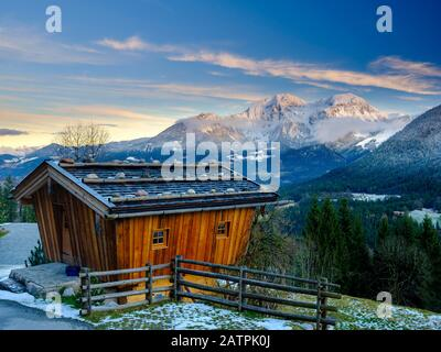 Traditional wooden hut, behind it the massif of the Hohen Goell in winter, Berchtesgaden National Park, Schoenau am Koenigssee, Berchtesgadener Land - Stock Photo