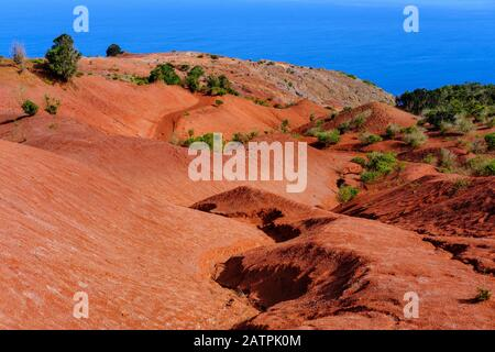 Eroded mountain slope with red earth, near Agulo, La Gomera, Canary Islands, Spain - Stock Photo