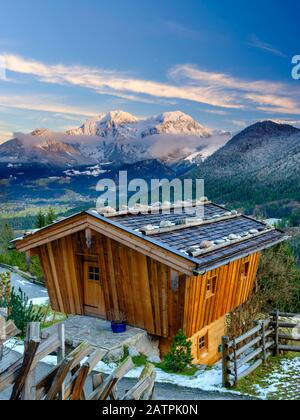 Traditional wooden hut, behind it the massif of the Hohen Goell in winter, Berchtesgaden National Park, Schoenau am Koenigssee, Berchtesgadener Land Stock Photo
