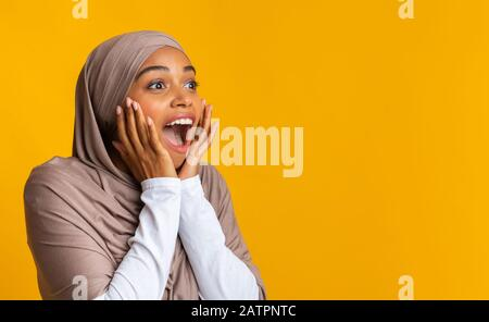 Black girl in headscarf looking at copy space, exclaiming in amazement - Stock Photo