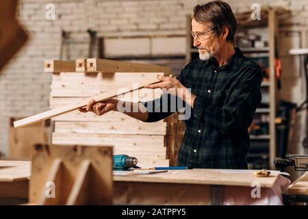 Male carpenter checking straightness of a wooden plank in workshop - Stock Photo