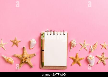 notebook with sseashells on pink background top view flat lay. Planning summer holidays, tourism and vacation concept. - Stock Photo