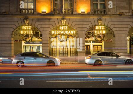 The Ritz Hotel and Restaurant lit up at night with Christmas decorations hanging. Long exposure with the lights of cars passing in front. London - Stock Photo