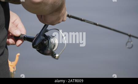 Male hand holding fishing rod and reeling the other hand. - Stock Photo