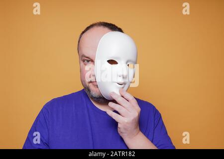 adult man taking off mask revealing face and identity - Stock Photo