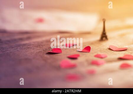 Lovely romantic Eiffel Tower miniature with red little hearts on wooden surface with space for text. Background for valentine's day, wedding, gift, gr - Stock Photo