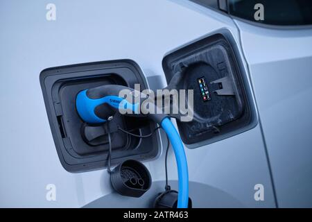Nuremberg, Germany - January 14, 2020: Close-up of a charging plug from Mennekes connected with the charging socket of a silver colored electric car a - Stock Photo