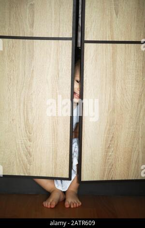 Toddler girl plays hide and seek, she hid behind the cabinet doors and peeks from there. - Stock Photo