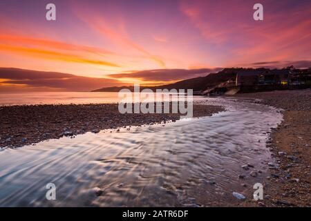 Charmouth, Dorset, UK.  4th February 2020. UK Weather.  A spectacular fiery sunset at the beach at Charmouth in Dorset looking west along the coast towards Lyme Regis.  Picture Credit: Graham Hunt/Alamy Live News - Stock Photo