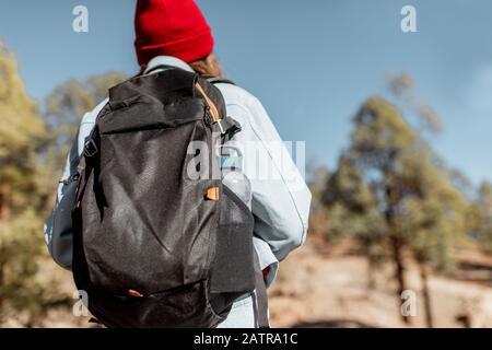 Young woman dressed casually walking with backpack in the forest highly in the mountains on the volcanic rocks
