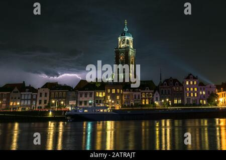 Stunning night image of lightning over a river and historic city of Deventer, the Netherlands. - Stock Photo
