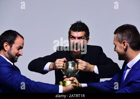 Coworkers or partners fight for winning competition. Businessmen with mad faces in formal suits on grey background. Rivalry and business confrontation concept. Company leaders hold golden prize - Stock Photo