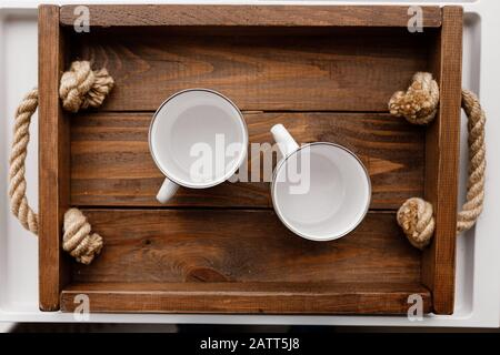 Top flat view of two white empty cups on rustic wooden tray and background. Cozy home, lovely breakfast with beloved - Stock Photo
