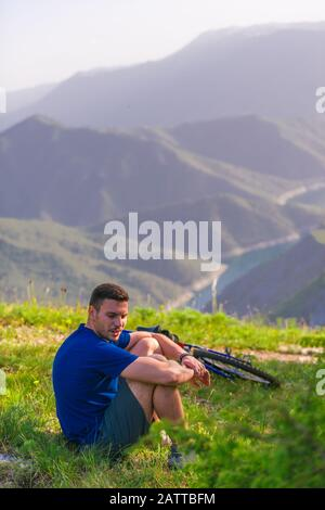 Tired athlete sits on green grass next to his bicycle while enjoying the beautiful view. - Stock Photo