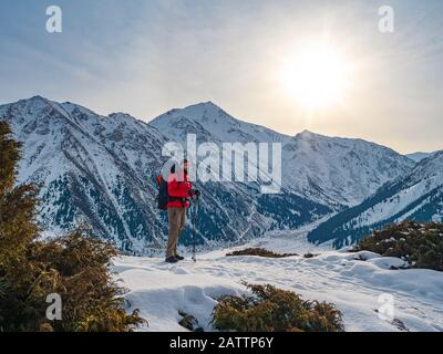 A tourist in a bright red jacket stands against the backdrop of a magnificent mountain landscape on a sunny morning. Big Almaty Lake. Kazakhstan - Stock Photo
