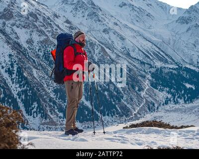 A tourist in a bright red jacket stands against the backdrop of a magnificent mountain landscape on a sunny morning - Stock Photo