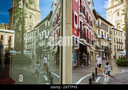 Granada, Andalusia, Spain - October 31st, 2019 : tourists walk past a store window reflecting the tower of the cathedral. - Stock Photo