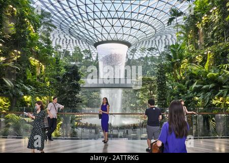 Tourists taking souvenir photos in front of the 40m high indoor waterfall at Jewel Changi, a shopping mall attached to Changi Airport, Singapore - Stock Photo
