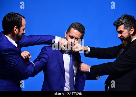 Business conflict and argument concept. Coworkers decide upon best working position. Company leaders fight for business leadership. Businessmen with rage faces in formal wear on blue background - Stock Photo