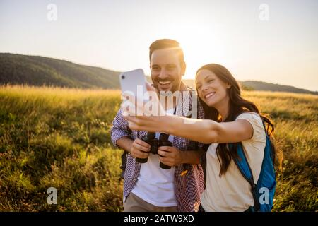 Happy couple is hiking in mountain. They are taking selfie.