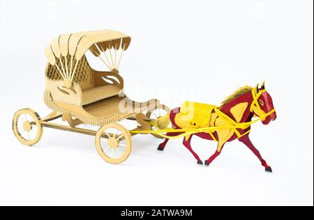 Side view of a decorated horse made of cardboard pulling a cardboard carriage on a white background - Stock Photo