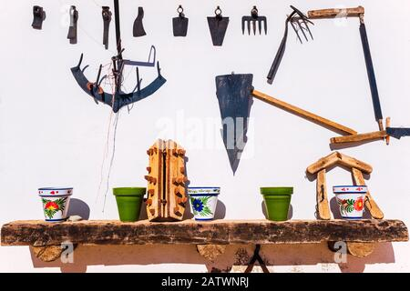 Old farm tools and colorful decorated terracotta pots, on a white wall in the sun. - Stock Photo