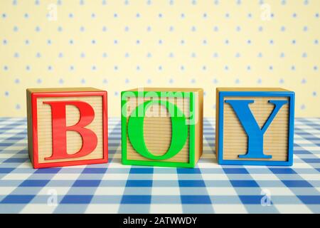 Childrens wooden ABC blocks spelling BOY on a checked tablecloth - Stock Photo