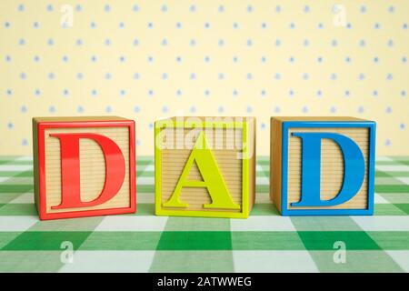 Childrens wooden ABC blocks spelling DAD on a checked tablecloth - Stock Photo