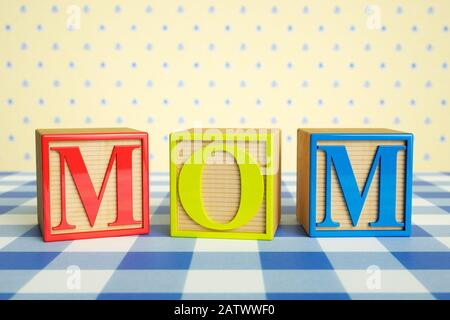 Childrens wooden ABC blocks spelling MOM on a checked tablecloth - Stock Photo