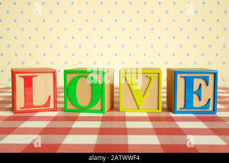 Childrens wooden ABC blocks spelling LOVE on a checked tablecloth - Stock Photo