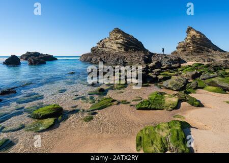 Woman on the rocks at Praia da Samoqueira beach in Portugal