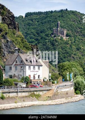 RHINELAND-PALATINATE, GERMANY - 7/6/2019:  The riverside restaurant Klosterschenke  with Maus Castle set on a hillside overlooking the Rhine River