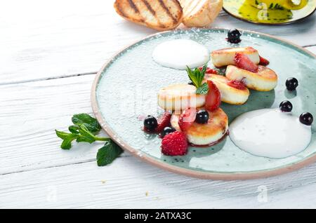 Cheese pancakes with strawberries and sour cream. Breakfast. In the plate. Top view. Flat lay composition Free copy space. - Stock Photo