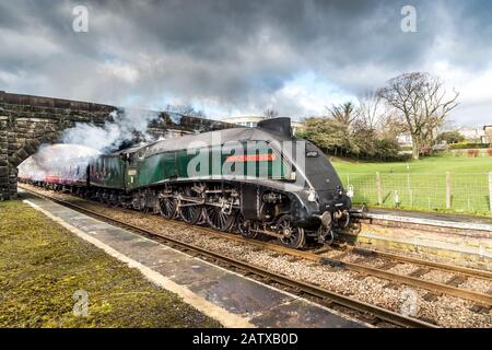 The famous LMS Class A4 4-6-2 60009 Union of South Africa steam train travelling at speed through High Bentham in North Yorkshire - Stock Photo
