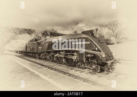 The famous LMS Class A4 4-6-2 60009 Union of South Africa steam train in monochrome travelling at speed through High Bentham in North Yorkshire - Stock Photo