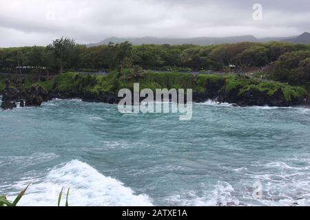Waves crashing into the rocky, volcanic shoreline of the bay in Waianapanapa State Park, Hana, Maui, Hawaii, USA with the boardwalk along the shore in - Stock Photo