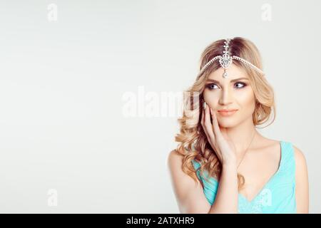 Look here. Woman blonde curly hair in tikka oriental jewelry on head looking to the side smiling hand on face cheek isolated white gray background wal - Stock Photo