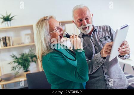 Senior couple singing karaoke at home, having fun. - Stock Photo