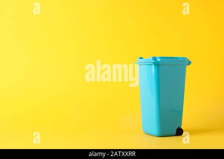 Blue recycle bin on yellow background, space for text - Stock Photo