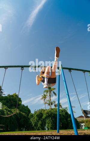 Teenage girl swinging high in children's playground equipments at Tauranga Domain, New Zealand.