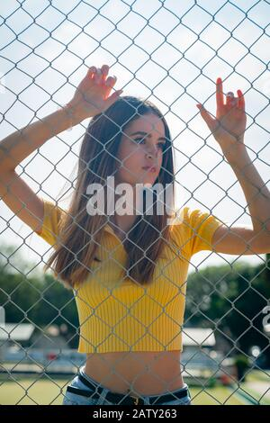 Teenage girl in yellow top standing with arms raised behind chain link fence with arms up holding on. - Stock Photo