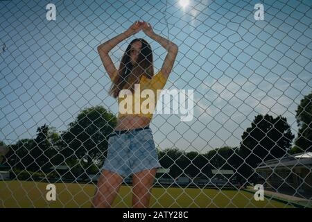 Teenage girl in yellow top standing with arms raised behind chain link fence with arms up holding on and fence shadows. - Stock Photo