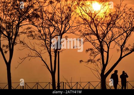 Silhouette of two people in the park with an intense orange atmosphere produced by the back light of the sunset - Stock Photo