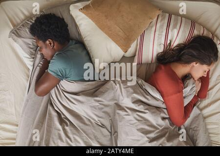 Young multiethnic couple lying back to back in bed and sleeping in the bedroom - Stock Photo
