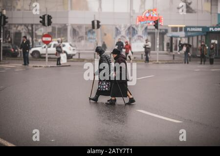 Bucharest, Romania - December 20, 2019: Two old women illegally cross the road in the middle of a crossroad. - Stock Photo